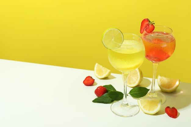 Bicchieri di cocktail estivi freschi su sfondo giallo