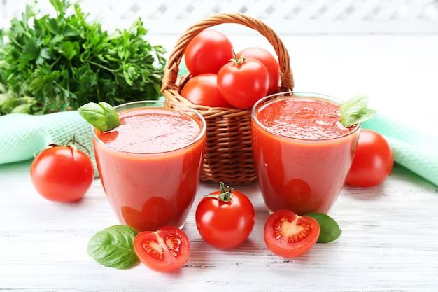 Bicchieri di succo di pomodoro fresco sul tavolo di legno, primo piano