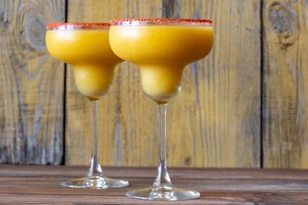 Bicchieri di cocktail margarita al mango congelato guarniti con bordo di sale alla paprika