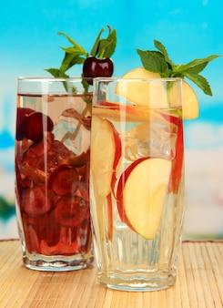 Bicchieri di bevande alla frutta con cubetti di ghiaccio su blue