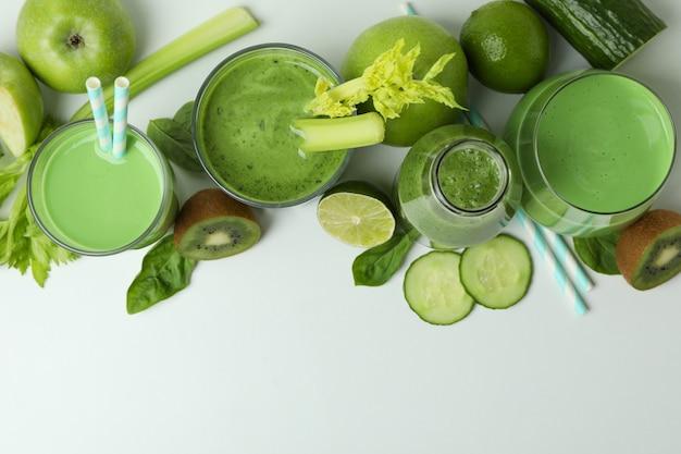 Bicchieri di frullato verde e ingredienti su sfondo bianco, vista dall'alto