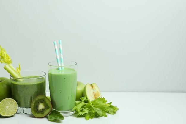 Bicchieri di frullato verde e ingredienti sul tavolo bianco