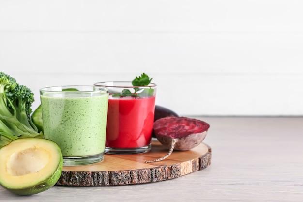 Bicchieri di frullato sano e verdure sulla superficie in legno chiaro