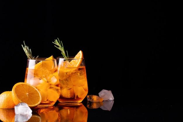Bicchieri di cocktail aperol spritz ghiacciato su sfondo nero