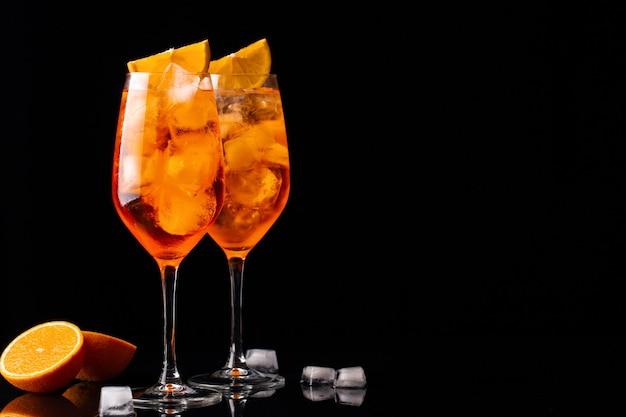 Bicchieri di cocktail aperol spritz ghiacciato servito in un bicchiere di vino su sfondo nero