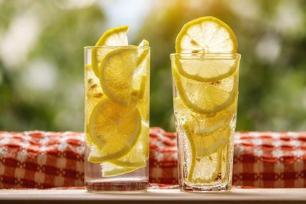 Bicchieri di limonata al limone sul giardino soleggiato