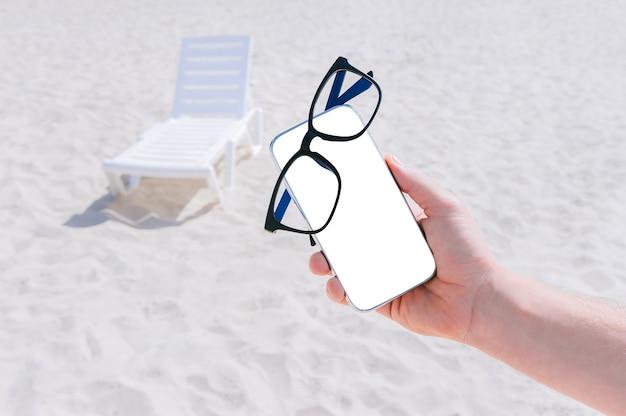 Occhiali sul modello di uno smartphone nella mano di un uomo. sullo sfondo della spiaggia e delle sedie a sdraio.