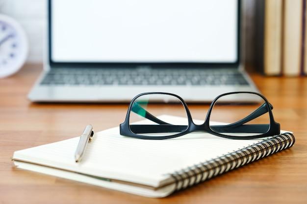 Occhiali e blocco note con computer portatile con schermo vuoto sul ponte, posto di lavoro con il computer portatile sul tavolo a casa, concetto di casa forma di lavoro