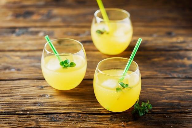 Bicchieri di cocktail all'arancia con ghiaccio e menta, tavolo in legno e messa a fuoco selettiva