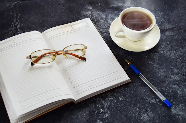 Occhiali, una penna, un taccuino e una tazza di caffè su sfondo scuro strutturato
