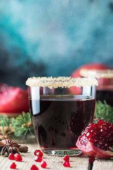Un bicchiere di succo di melograno con frutti di melograno fresco e rami di abete sulla tavola di legno. concetto di bevanda sana.