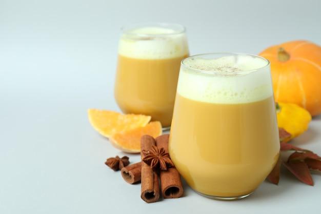 Bicchieri di latte di zucca e ingredienti su sfondo grigio chiaro