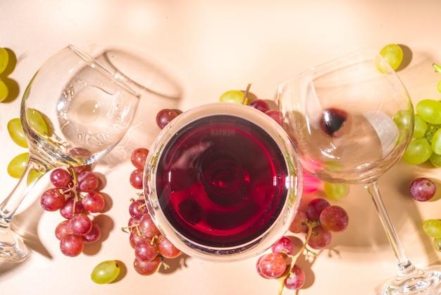 Bicchieri di vino rosso e bianco con sole e ombre, con bottiglia e decanter, grappolo d'uva, su sfondo di colore cremoso, vista dall'alto flatlay degustazione di vini, vendemmia autunnale, concetto di cantina