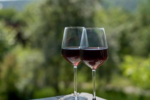Bicchieri di vino rosso su sfondo verde giardino, all'aperto.