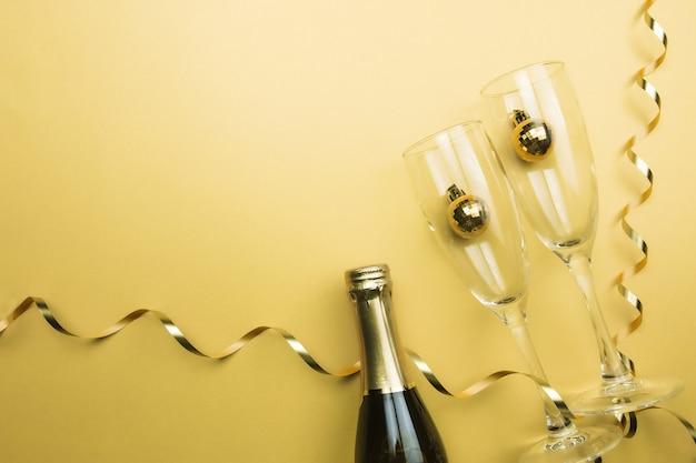Bicchieri, bottiglia di spumante, palline dell'albero di natale, nastro, fondo oro