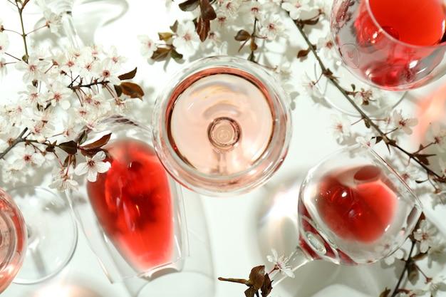 Bicchieri di vino e fiori di ciliegio su sfondo bianco