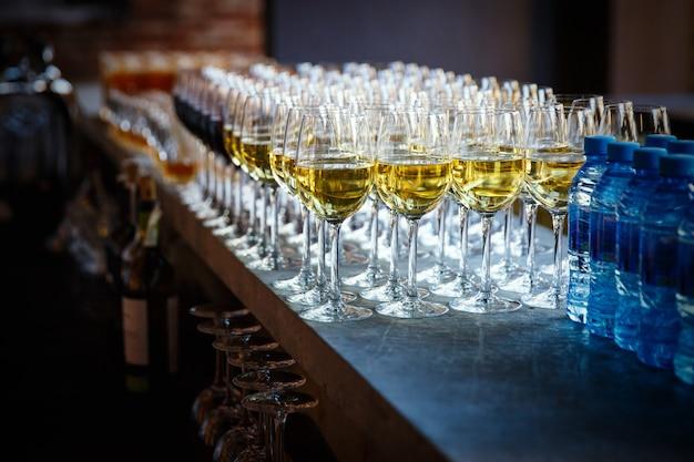 Bicchieri di champagne in fila con bottiglie d'acqua