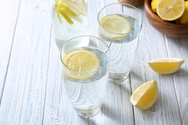 Bicchieri con acqua fredda al limone sul tavolo in legno chiaro