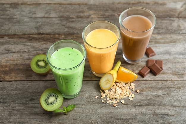 Bicchieri con diversi frullati di proteine sul tavolo di legno