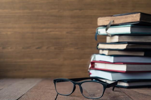 Occhiali con libri con copertina rigida sulla tavola di legno. spazio libero per il testo messa a fuoco selettiva