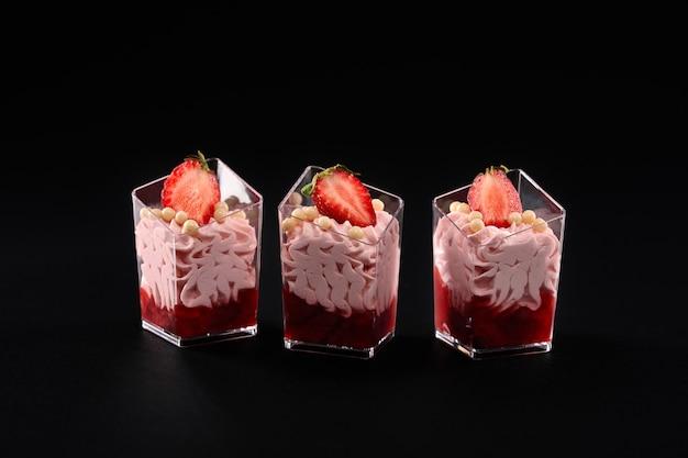 Bicchieri con marmellata, panna montata e fragole in fila.