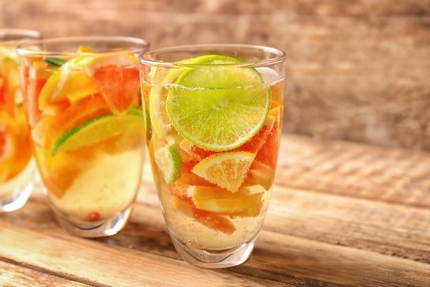 Bicchieri con rinfrescante cocktail di agrumi su legno