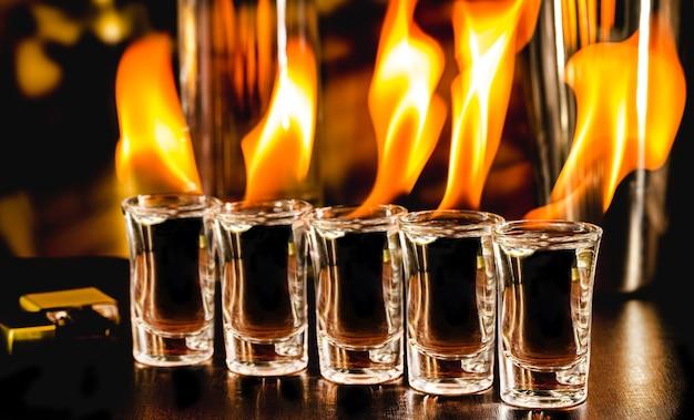 Bicchieri con colpi di tequila in fiamme, bevanda fiammeggiante