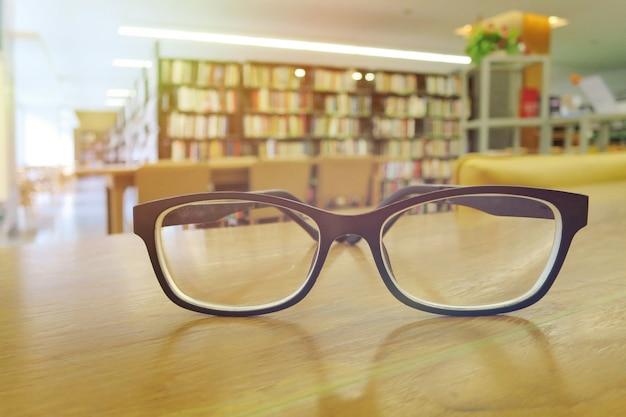 Un bicchieri sul tavolo di legno in biblioteca.