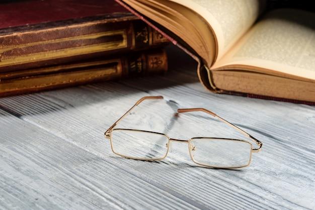 Bicchieri su un tavolo di legno accanto a vecchi libri. concetto di apprendimento.