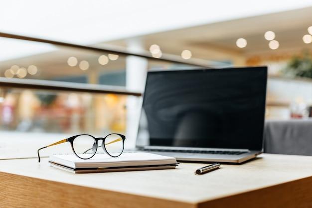 Occhiali sul posto di lavoro in ufficio vicino al computer portatile e al blocco note