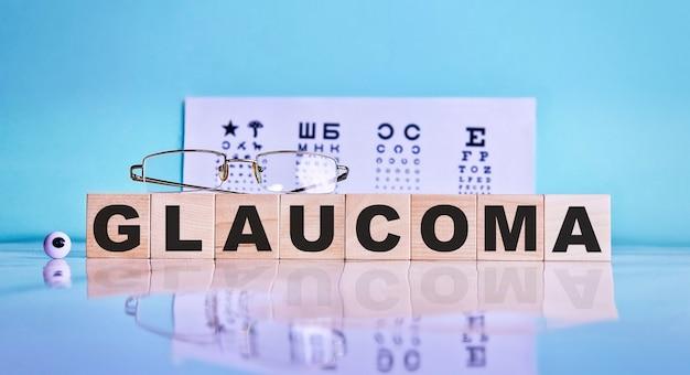 Parola glaucoma scritta su cubi di legno, occhiali, occhi sullo sfondo di un tavolo di prova dell'occhio.