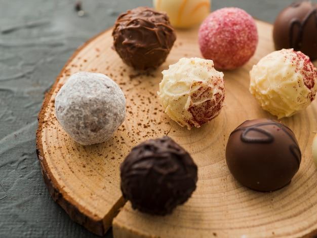 Caramelle di cioccolato smaltato su piatto di legno tagliato