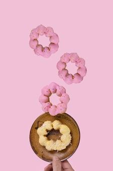 Ciambelle glassate in levitazione con sfondo di colore rosa tenue.