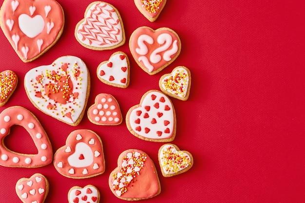 Glassato con biscotti a forma di cuore di glassa su sfondo rosso