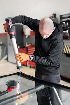 Vetraio applicando guarnizioni in gomma al parabrezza in garage, primi piani. foto di alta qualità