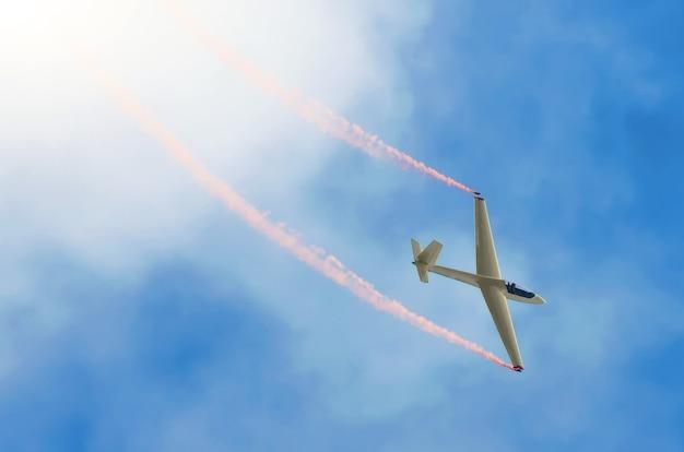 Aereo aliante che vola alto nel cielo con una traccia di fumo rosso.