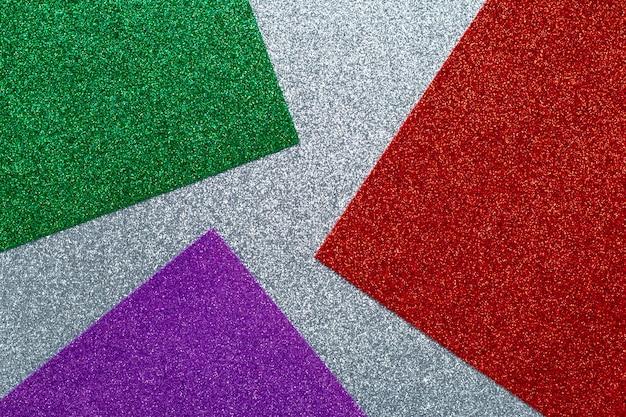 Parete glitterata, trama scintillante. superficie lucida, modello lucido astratto. carta artigianale grigia, verde, rossa e viola, tessuto con paillettes, tessuto.