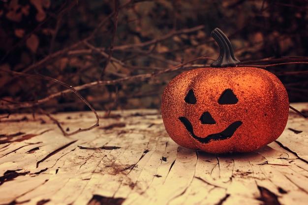 Zucca di halloween scintillante sulla scrivania in legno. decorazione spettrale stagionale autunnale