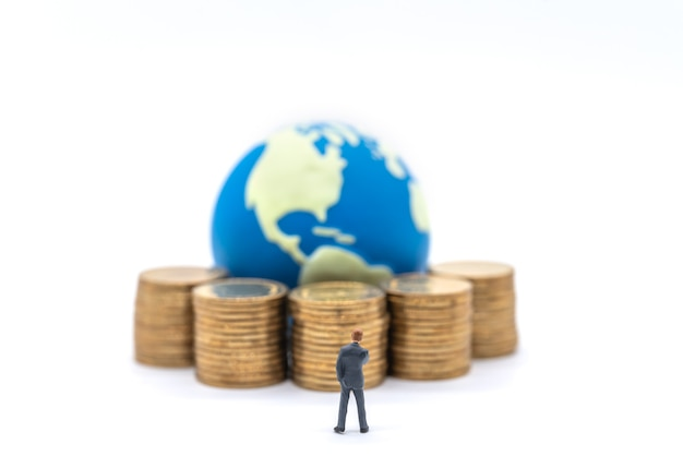 Business globale e concetto finanziario. imprenditore in piedi in miniatura e cercando di pila di monete d'oro con mini palla del mondo su sfondo bianco.