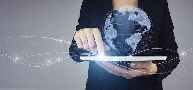 Concetto di connessione globale. compressa bianca in mano della donna di affari con il segno digitale del pianeta dell'ologramma su fondo grigio. concetto di mappe e navigazione internet.