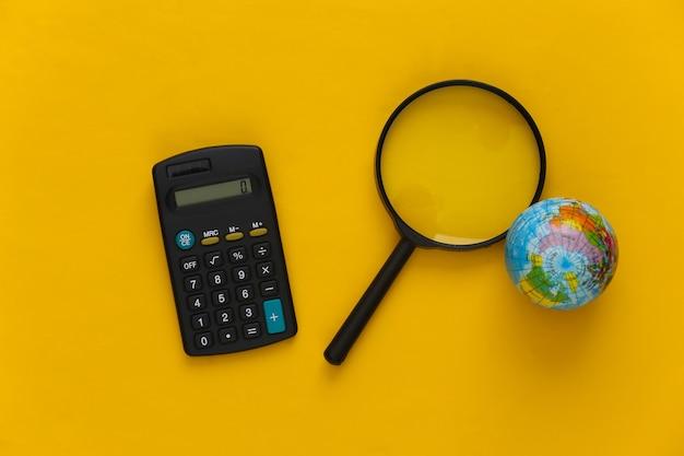 Crisi globale. lente d'ingrandimento con globo e calcolatrice su giallo