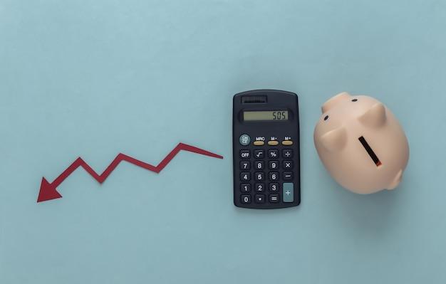 Tema della crisi globale. calcolatrice con salvadanaio, freccia cadente che tende verso il basso sul blu
