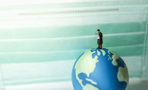Global healthcare, covid-19 e informazioni. imprenditore figura in miniatura persone in piedi e leggendo il giornale sulla mini sfera del mondo con maschera chirurgica come sfondo.