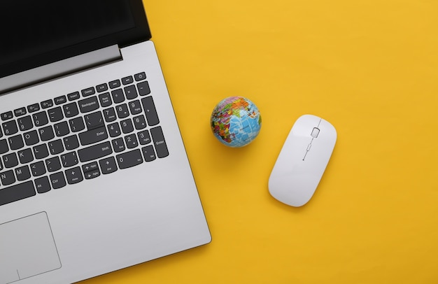Rete globale. computer portatile con mouse per pc e globo su sfondo giallo. vista dall'alto. lay piatto