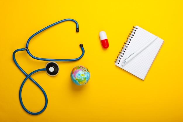 Pandemia globale ancora in vita. globo, stetoscopio, capsula, blocco note su uno sfondo giallo. vista dall'alto. focolaio di coronovirus