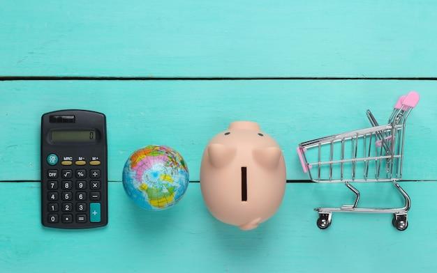 Idee di acquisto globali. globo con salvadanaio, carrello del supermercato, calcolatrice su una superficie di legno blu. concetto di risparmio. vista dall'alto