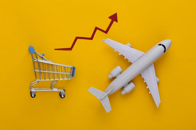 Supermercato globale. aumento delle spedizioni internazionali. carrello della spesa e aereo con freccia di crescita su giallo