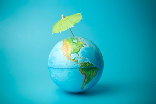 Il riscaldamento globale e il cambiamento climatico sul concetto di terra. globo terrestre con un ombrello. proteggere l'atmosfera dalle radiazioni ultraviolette e dai buchi dell'ozono