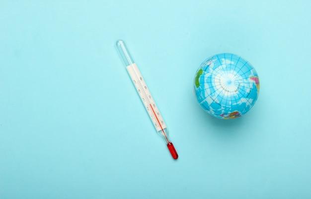 Il riscaldamento globale ancora in vita. globo e termometro sulla parete blu questioni climatiche globali. concetto di eco