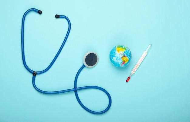 Il riscaldamento globale ancora in vita. globo e termometro, stetoscopio sulla parete blu questioni climatiche globali. trattamento del pianeta terra. concetto di eco